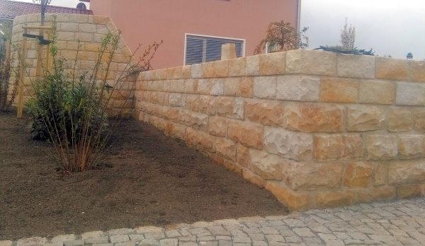 Sandsteinmauer, runder Grillplatz von außen betrachtet, Fußweg mit Granit